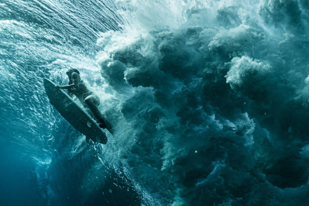 Underwater view of the woman surfer passing the powerfull ocean wave stock photo