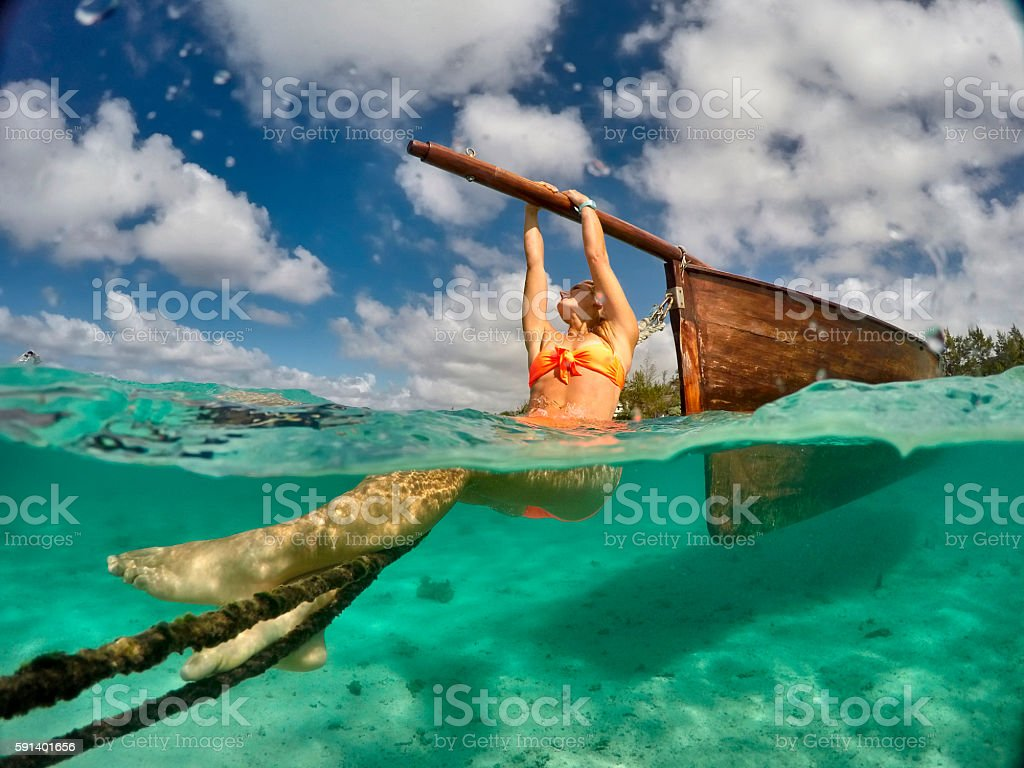 Underwater view of woman hanging onto wooden boat stock photo