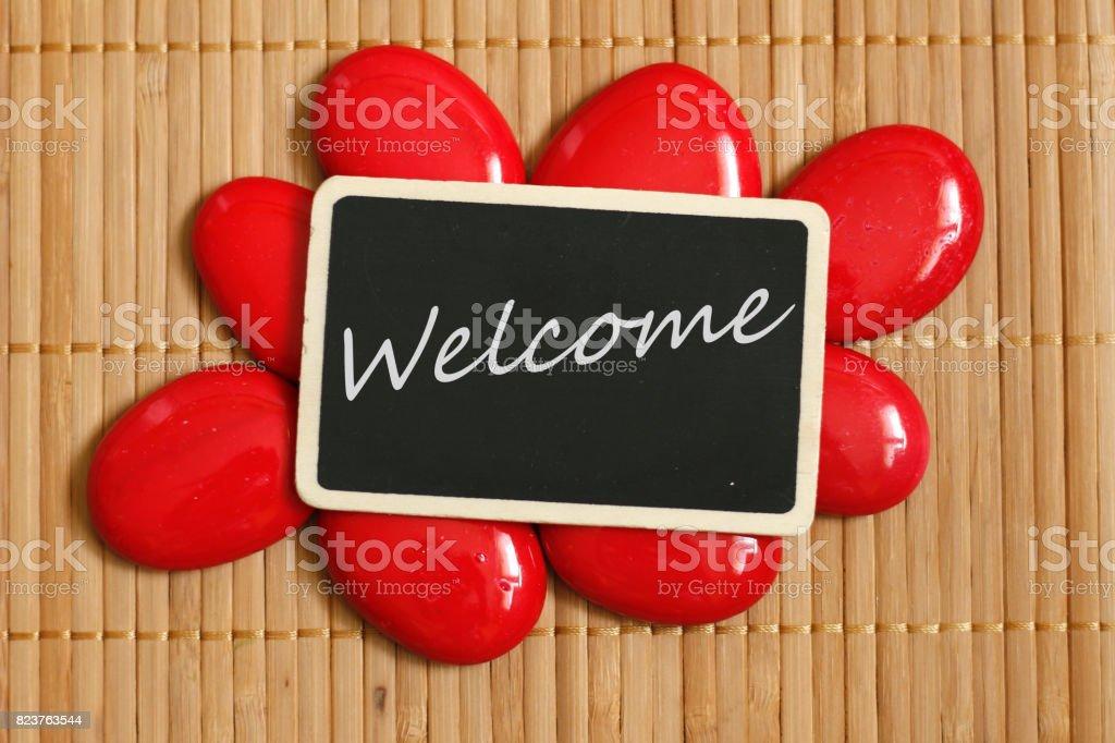 une ardoise avec un message bienvenue en anglais entourée de galet rouge et sol de bambou stock photo