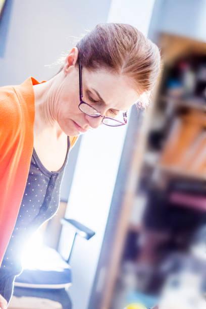 Une femme et son oeuvre. Une femme avec un chandail de couleur orange peint un oeuvre. Une seconde oeuvre est disposée sur un plateau à la verticale. entreprise stock pictures, royalty-free photos & images