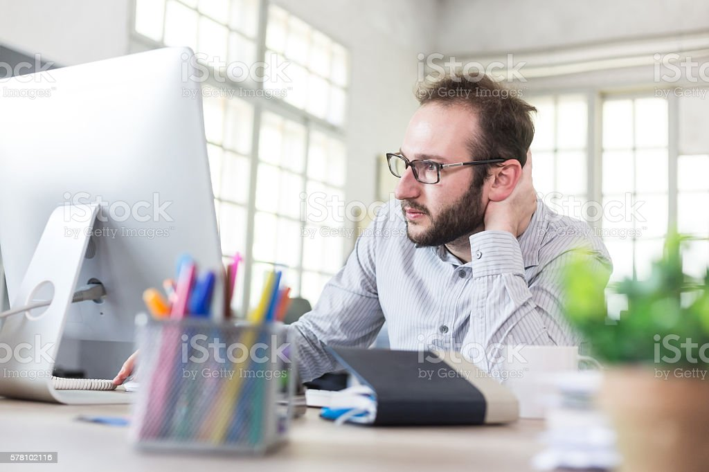 Uneasy young businessman with eyeglasses at workplace stock photo