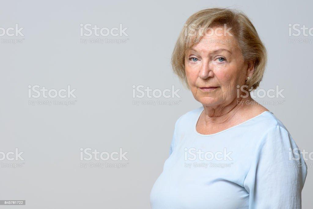 Unemotional attractive elderly woman stock photo