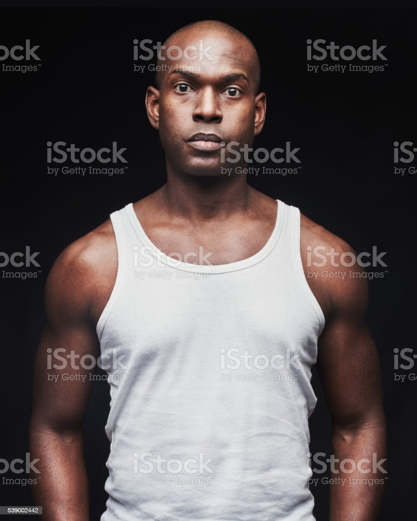 Unemotional young black man in tank top stock photo