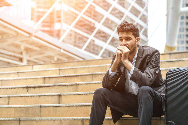 Unemployed businessman stress sitting on stair, concept of business failure and unemployment problem, work life balance, image processing instagram vintage color. stock photo