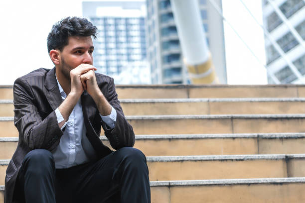 Unemployed businessman stress sitting on stair, concept of business failure and unemployment problem, work life balance. stock photo