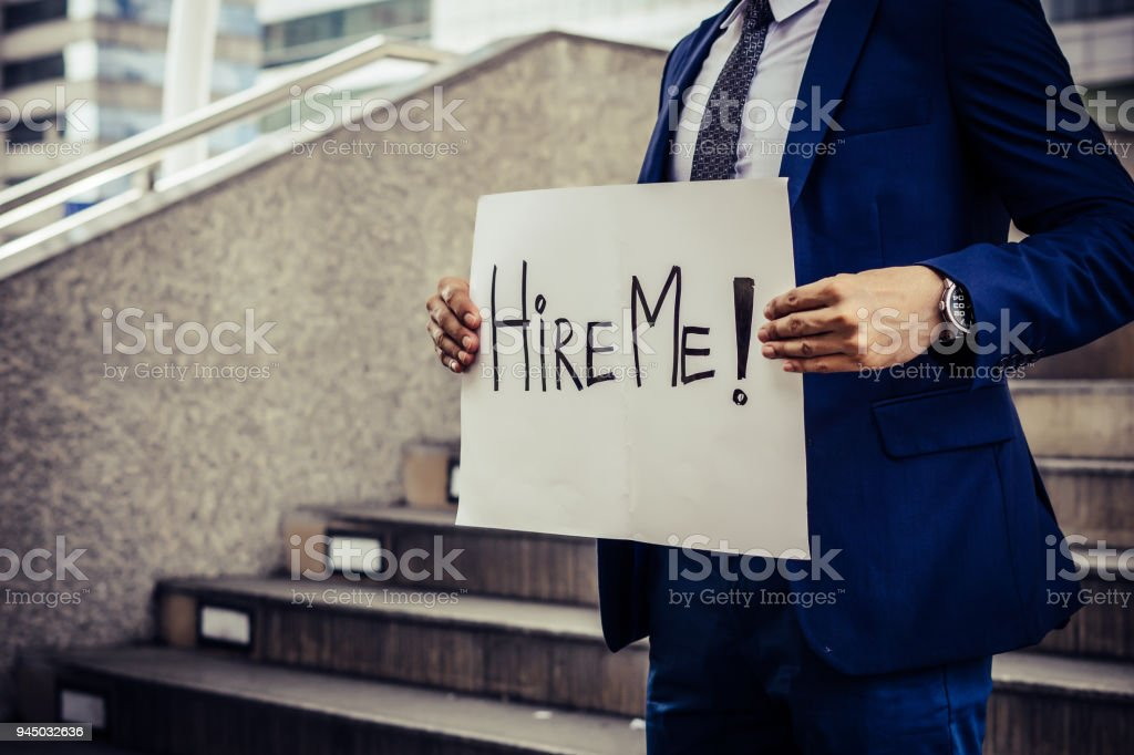 Unemployed man desperately looking for a job. Holding a need a job sign. stock photo