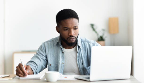 Unemployed man using laptop searching for vacancies online in internet Job search. Unemployed man using laptop searching for vacancies online in internet and taking notes, panorama with copy space applicant stock pictures, royalty-free photos & images