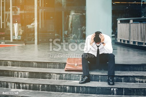 1018458132istockphoto Unemployed Tired or stressed businessman sitting on the walkway after work Stressed businessman concept 845772748