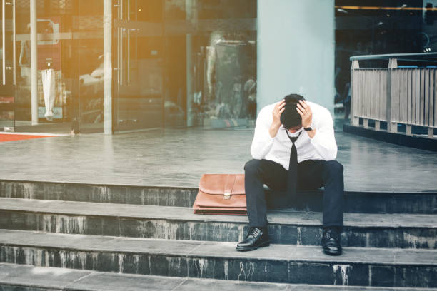 Unemployed Tired or stressed businessman sitting on the walkway after work Stressed businessman concept Unemployed Tired or stressed businessman sitting on the walkway after work Stressed businessman concept downsizing unemployment stock pictures, royalty-free photos & images