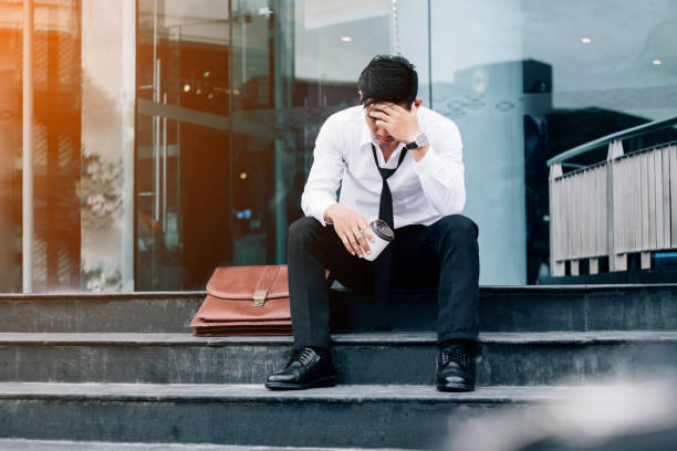 unemployed tired or stressed businessman sitting on the walkway after work stressed businessman concept - unemployment stock pictures, royalty-free photos & images
