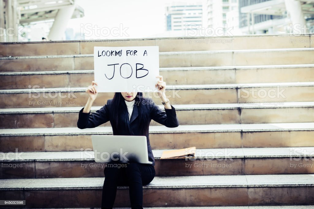 Unemployed woman desperately looking for a job. Holding a need a job sign. stock photo