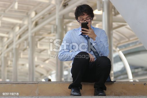 istock Unemployed young Asian man looking for job in mobile smart phone. Unemployment people concept. 925119218