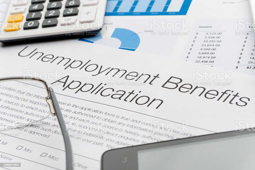 Unemployment benefits application form with paperwork Unemployment benefits application form with paperwork and mobile phone. Close up Application Form Stock Photo