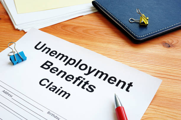 Unemployment benefits claim and stack of documents. stock photo