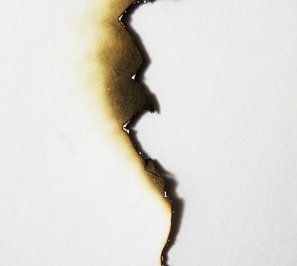 uneven burned edge of a piece of paper - verbrand stockfoto's en -beelden