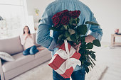 istock Unexpected moment in routine everyday life! Cropped photo of man's hands hiding holding chic bouquet of red roses and gift with white ribbon behind back, happy woman is on blurred background 925492142