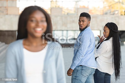 istock Unfaithful guy looking at another woman while walking with his girlfriend 1188587944