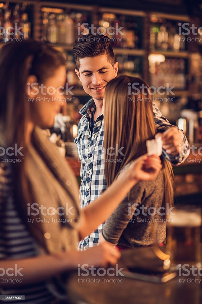 Unfaithful man giving his phone number in a cafe. stock photo