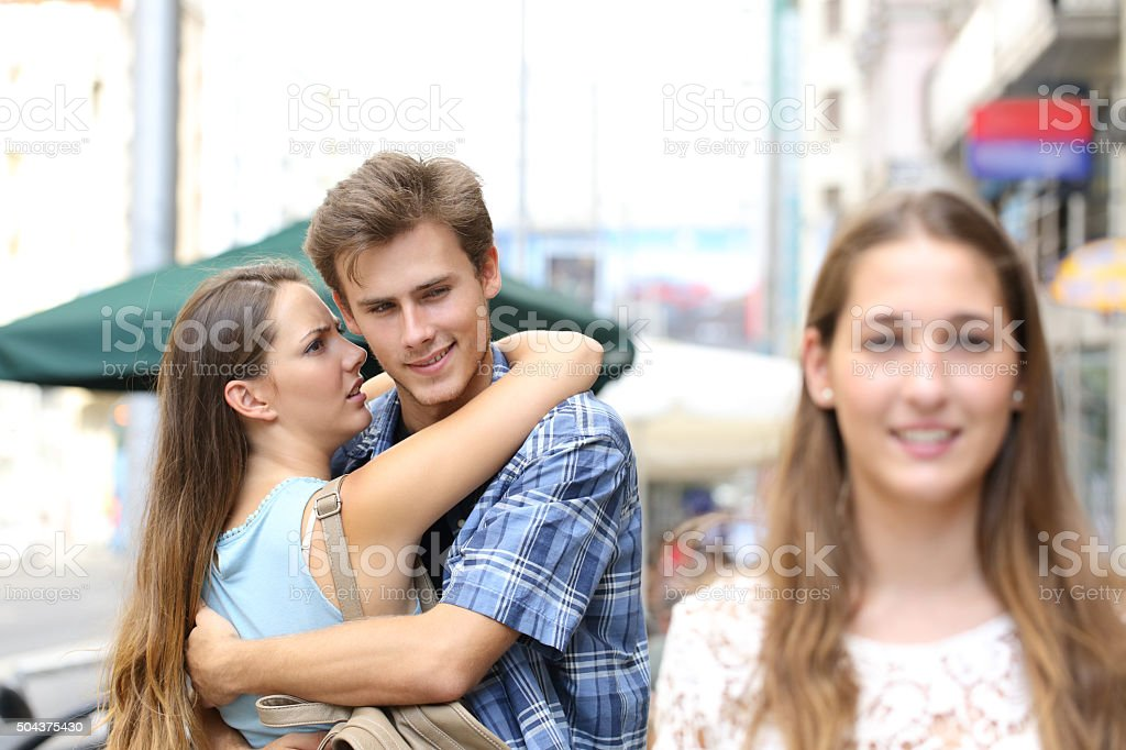 Unfaithful man hugging his girlfriend and looking another royalty-free stock photo