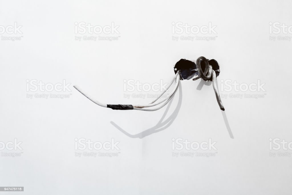 Unfinished electrical  mains outlet socket  with electrical wires with black adhesive tape installed in plasterboard or drywall for gypsum walls  in apartment is under construction and remodeling stock photo