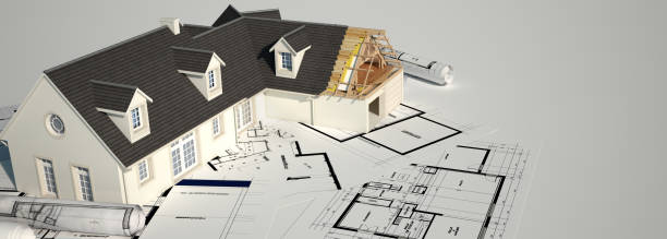 Unfinished house on top of blueprints stock photo