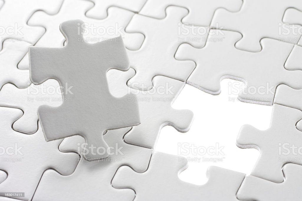 Unfinished jigsaw puzzle and last piece. royalty-free stock photo