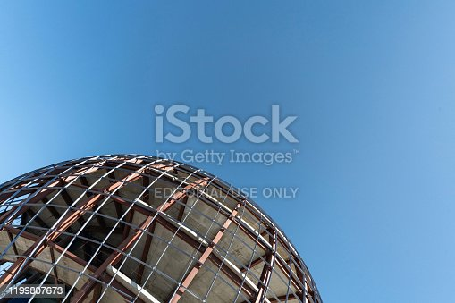 Unfinished sphere shape building, copy space. Construction of futuristic shopping mall or museum. Building constructed of concrete and reinforcement.