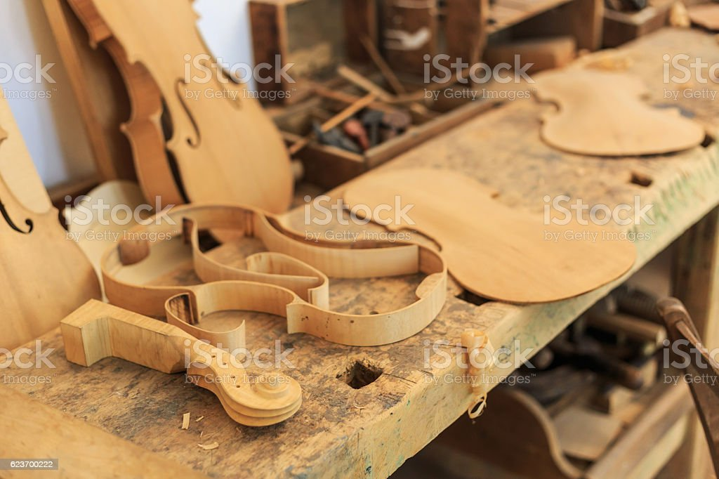 Unfinished violin and wooden tools in workshop stock photo