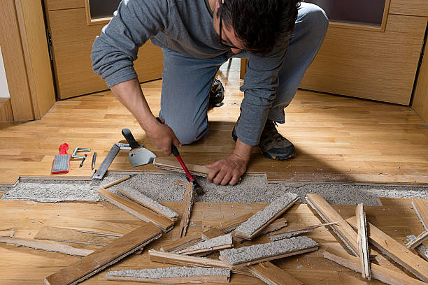 Unfixing Wooden Floor Manual worker disassembling wooden floor ruined from moisture and water leak.   detach stock pictures, royalty-free photos & images