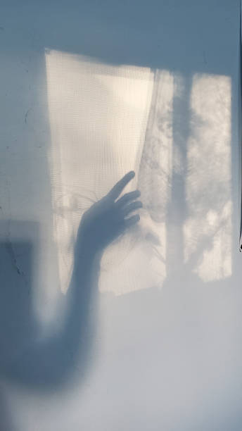Unfocused silhouette in shape of hand gesture touching lace curtain shadow stock photo