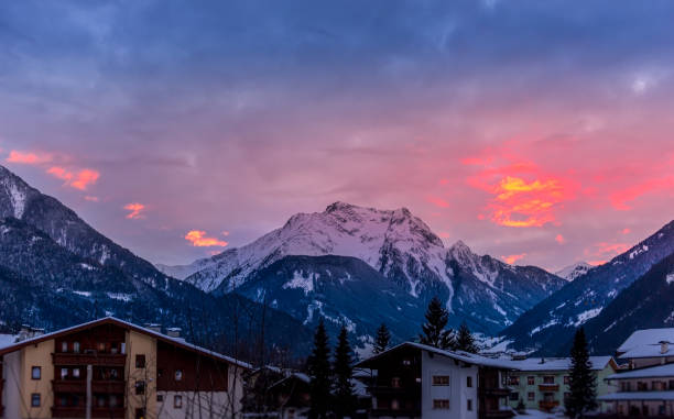 Unfocused ski lodge below a stunning sunset with snowcapped mountains stock photo