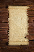 istock Unfolded paper scroll on a wooden surface, blank background 837800040