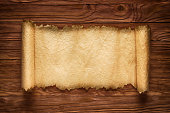 istock Unfolded scroll on a wood table, old paper texture, background 831744758