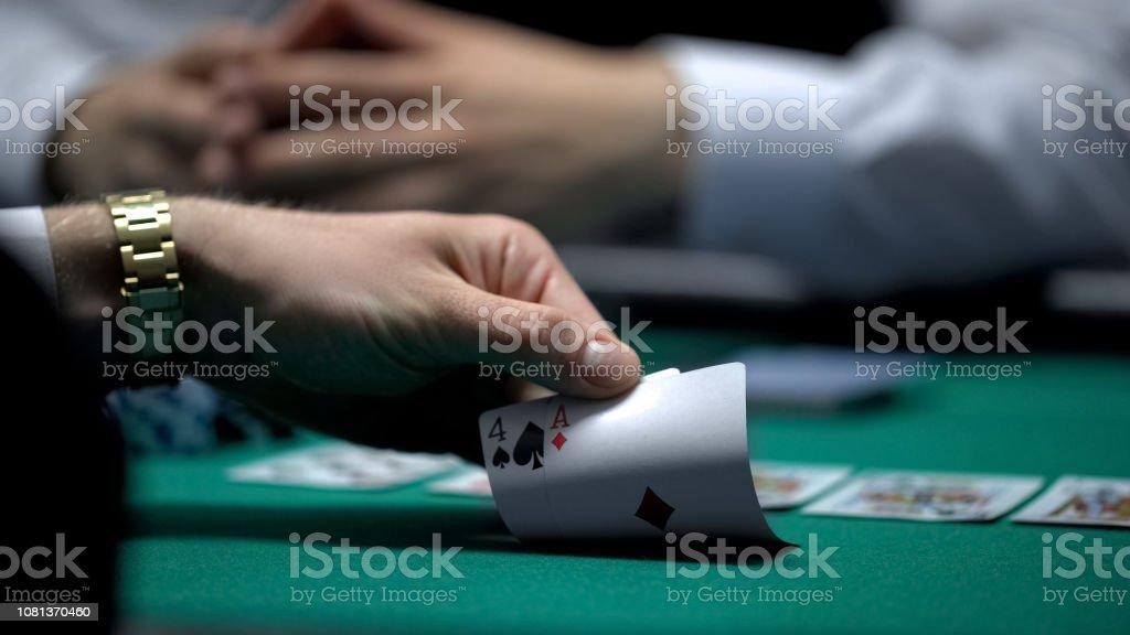 Unfortunate poker game, hand of casino player checking bad card...