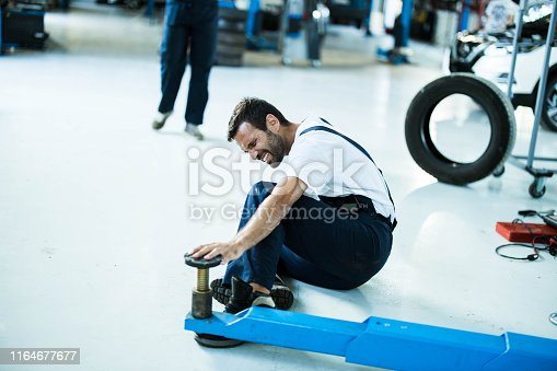 Young auto mechanic feeling terrible pain after crushed his feet with work tool in a workshop. Copy space.
