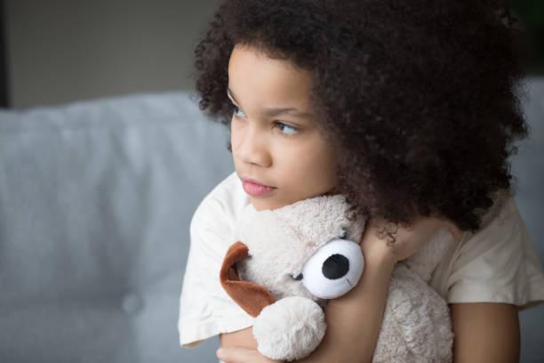 unglückliches streunendes biracial kind umarmen ausgestopftes spielzeug schaut beiseite - autismus stock-fotos und bilder