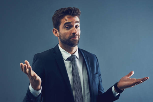 Unfortunately, I don't have all the answers Studio portrait of a handsome young businessman shrugging against a dark background shrugging stock pictures, royalty-free photos & images