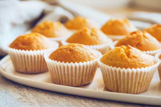 ungefrostete cupcakes auf einer weißen platte - vanille muffins stock-fotos und bilder