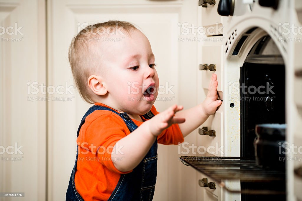 Unguarded baby with open oven stock photo