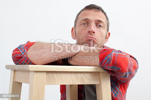expressive casual man concept - unhappy middle age man with checked shirt leaning on wooden stool expressing depression and frustration,white background