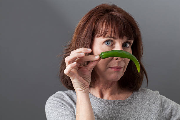 unglücklich 50er jahren reife frau fragen der geschmack von grünem pfeffer - sex sexuelle themen stock-fotos und bilder