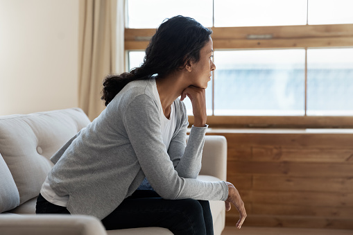 Unhappy young african american girl sit on sofa at home and looking at window, thinking about problem and trouble, suffering from depression or loneliness, mental illness, makes difficult decisions