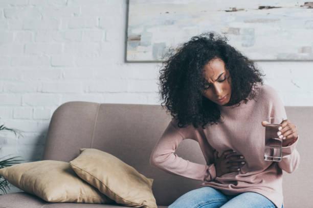 ongelukkige afro-amerikaanse vrouw die glas water vasthoudt terwijl hij op de bank zit en last heeft van maagpijn - buikpijn stockfoto's en -beelden