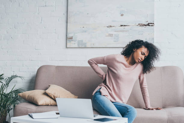 unhappy african american woman suffering from back pain while sitting on sofa near table with digital devices unhappy african american woman suffering from back pain while sitting on sofa near table with digital devices back pain stock pictures, royalty-free photos & images