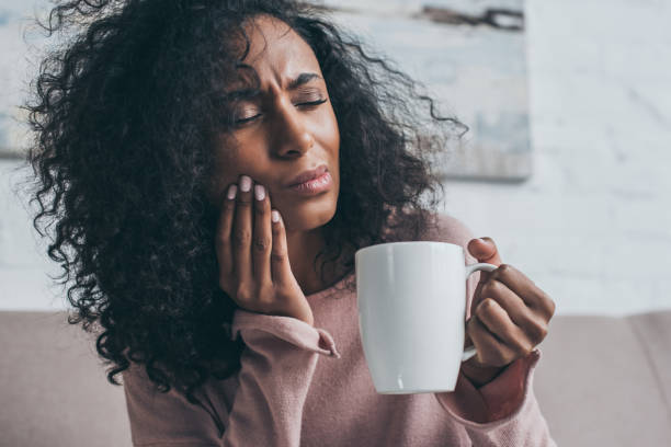 unhappy african american woman suffering from toothache and holding coffee cup stock photo