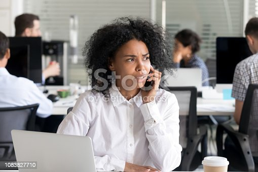 istock Unhappy African American woman talking on phone at workplace 1083827710
