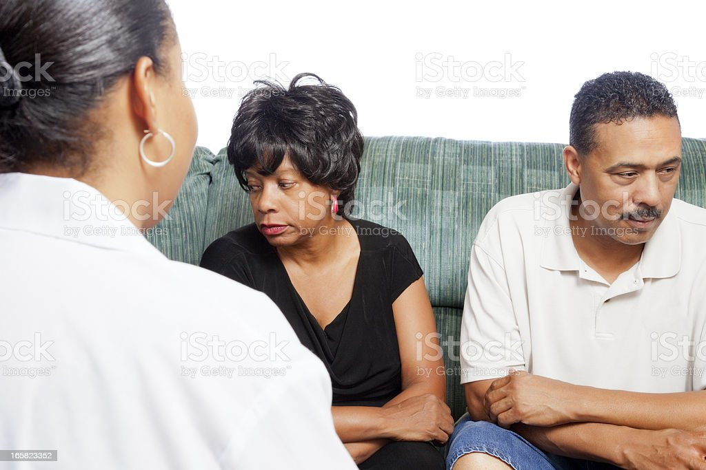 Unhappy african-american couple at the marriage counselor on white stock photo