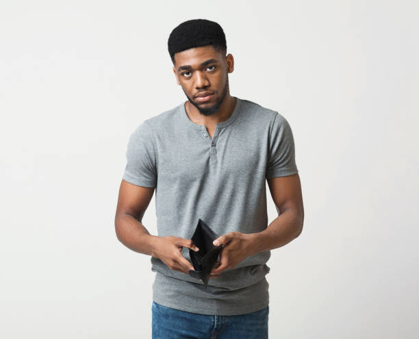 Unhappy african-american man showing empty wallet at studio stock photo