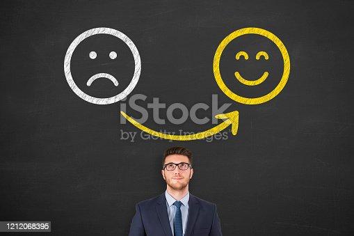 517629622 istock photo Unhappy and Happy over Human Head on Blackboard 1212068395