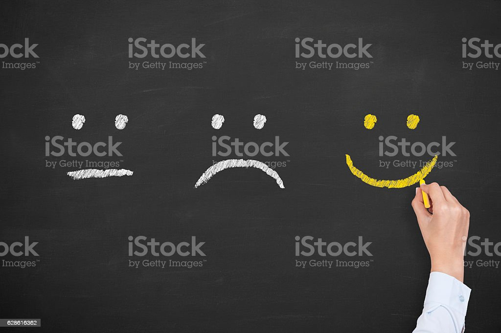 Unhappy and happy smileys on chalkboard stock photo